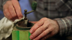 Elderly man cleaning a coffee mill. Close up. Stock Footage