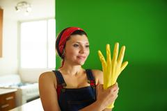 young hispanic woman with yellow latex gloves cleaning home - stock photo