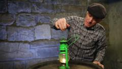 Man lighting an old oil lamp and observes it. Stock Footage