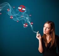 Young woman smoking dangerous cigarette with no smoking signs Stock Photos