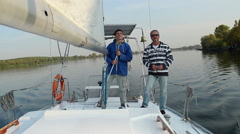 Two male sailors on deck of sailing yacht, friends, vacation Stock Footage