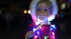 Cute Small Girl with Christmas Hat Puts Glow Stick in her Mouth - stock footage