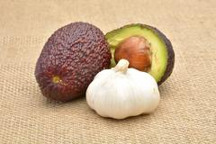 avocado and garlic on old canvas background - stock photo