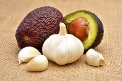 Avocado and garlic on old wooden background Stock Photos