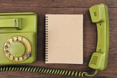 Vintage rotary telephone and notebook - stock photo