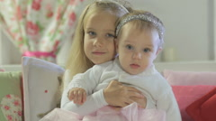 Beautiful little girl sitting with her little sister on the couch Stock Footage