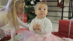 Little girl with long blond hair with her kid sister near Christmas tree Stock Footage