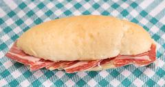 Side view of Serrano ham sandwich over checkered tablecloth Stock Photos