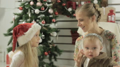 Stylish mother with two young daughters sitting next to beautiful Christmas tree Stock Footage