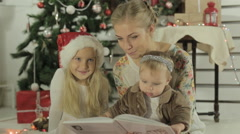 Beautiful mother reads fairy story to her little daughters Stock Footage