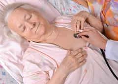 nurse taking the heartbeat of old woman - stock photo