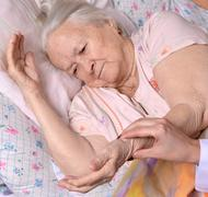 Female caretaker checking pulse of old woman Stock Photos