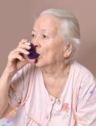 old woman with asthma inhaler - stock photo