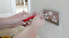 Electrician: removing a UK plug wall socket - stock footage
