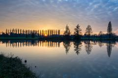Winter sunset in the shore of a lake with clouds reflected in the water Stock Photos