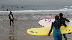 Young surfers entering the sea water Stock Footage