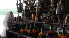 Tilt from candles to buddha statues in the Pak Ou Caves, Laos Stock Footage
