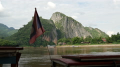 Flag from Laos at a longtail boat at the Pak Ou Caves Stock Footage
