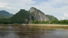 Mountain across the Pak Ou Caves with longtail boat passing by, Laos Stock Footage