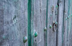 Old run-down green painted wooden door and iron nails - stock photo