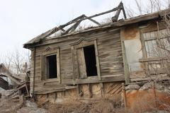 Deserted and a broken old wooden house in the city Stock Photos