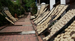 Woman walks through the streets in Luang Prabang with food drying in the sun Stock Footage