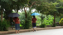 Girls walking with an umbrella in Luang Prabang, Laos Stock Footage