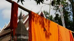 Stock Video Footage of Butterfly at orange monk robes at Wat aham luang prabang