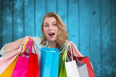 Composite image of overwhelmed young woman with shopping bags - stock photo