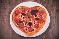 Heart shaped pizza on white plate Stock Photos