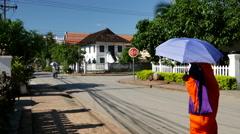 Monk with umbrella walking through the streets of Luang prabang Stock Footage