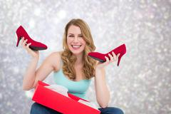 Composite image of smiling woman holding up her new shoes Kuvituskuvat