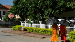 Monks with umbrella walking through the streets of Luang prabang Stock Footage