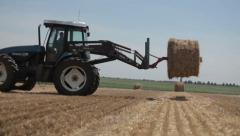 Tractor machine loading hay bales Stock Footage