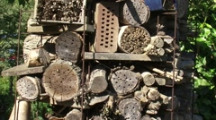 insect hotel, a structure of logs which offers nesting  + shelter for insects - stock footage