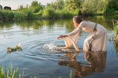 Attractive girl lowers wreath in water - stock photo