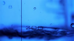Close-up of liquid in a measuring beaker is poured in the laboratory - stock footage