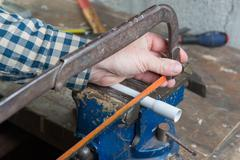 Man cut pvc pipe with a handsaw Stock Photos