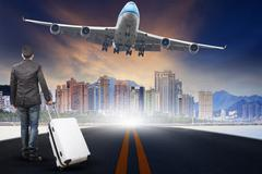 Young man with belonging luggage standing  against urban scen and passenger j Stock Photos