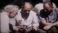 1457 - three guys try to figure out the camera - vintage film home movie Stock Footage