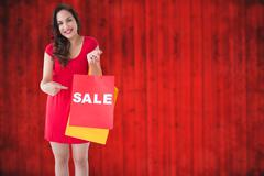 Composite image of astonished brunette holding a box Stock Photos
