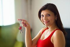 Stock Photo of portrait woman home owner smiling holding keys new house