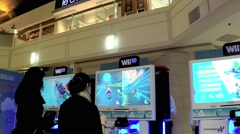 Wii staff demonstrates with people playing car racing game Stock Footage