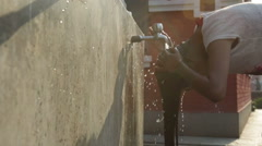 Kathmandu Nepal girl washes her hair in water spicket at childrens home in the Stock Footage