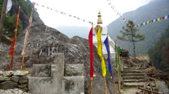 Nepal Himalayas  Prayer flags stand errect before a small Stupa along the path Stock Footage