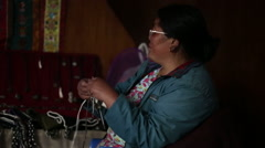 Himalayas Nepal Sherpa woman knits and watches television in tea house in the - stock footage