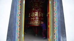 Nepal Himalayas  child spinning prayer wheel in Buhhdist shrine in the village Stock Footage