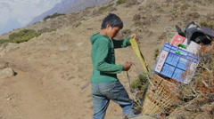 Himalayas Nepal Porter in Solukhumbu putting on load and walking away Himalayas Stock Footage