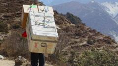 Himalayas Nepal Porter in Solukhumbu carrying load and walking away Himalayas Stock Footage