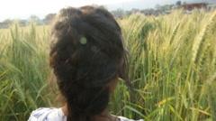Kathmandu Nepal young girl moving through wheat field in Eastern Kathmandu, Stock Footage